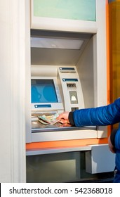 Man hand on atm taking money