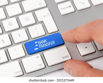 Man hand on the computer blue key with the lettering Bank transfer.Bank transaction or swift on internet concept.