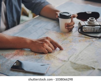 Man hand on the world map with coffee and vintage camera planing for travel concept