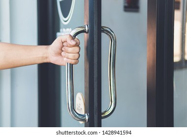 Man hand open the door with glass reflection background