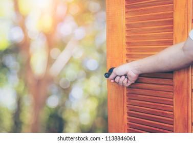 Man hand open door Handle the rocking shaft or opens empty room door to nature .