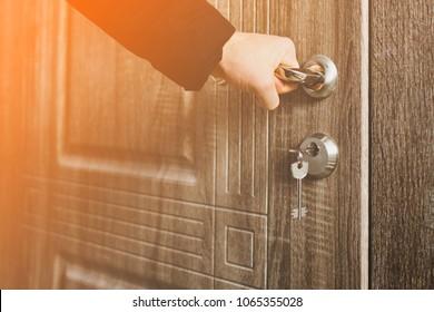 Man hand open doorknob in apartment. Open a door of a new apartent