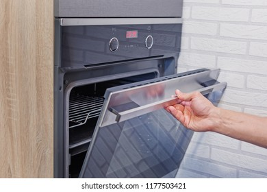 Man hand open electric oven, close up photo