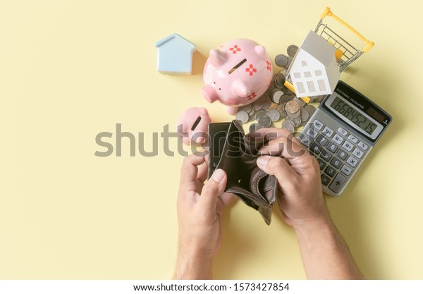 Man hand open an empty wallet with piggy bank and model house on yellow background, saving money concept