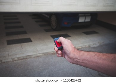 man hand open the garage door with remote control closeup