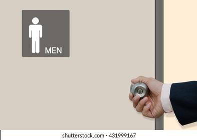 Man hand opening the  restroom door with toilet sign for men