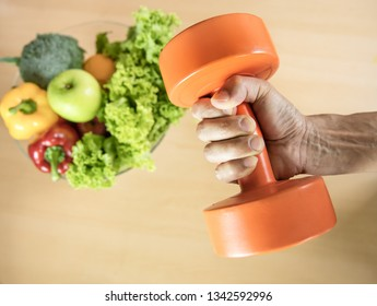 Man hand with orange Dumbbell with Healthy eating with Workout and fitness dieting ,fitness and weight loss concept, fruit, Vegetable on the table background