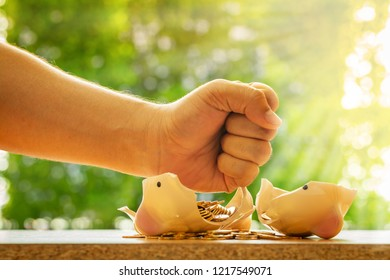 Man hand over which is raised above broken piggy bank with money in the public park, Loan and debt of business concept.