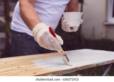 Man hand with paintbrush painting on a wooden table