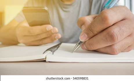 Man hand with pen writing on notebook and hold phone.