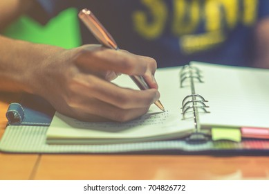 Man hand with pen writing on notebook. Young asian man writing form filling with register on paper notebook. Selective focus