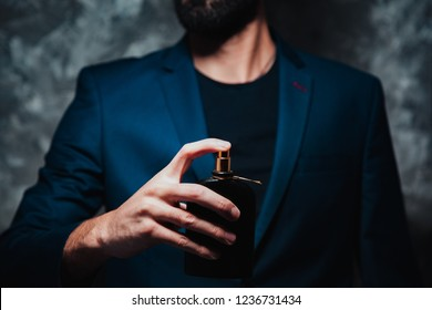 man hand perfume on gray background
