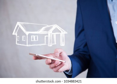 man hand phone and house in screen