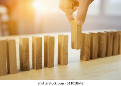 man hand pick one from many wooden blocks.business concept of choosing the right  amongst other ones,Planning,risk and strategy,businessman gambling investment,selective focus,vintage color