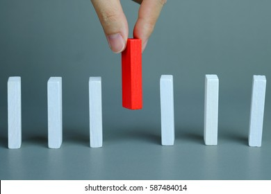 Man hand pick one of red wood block from many white wood block in row, metaphor to business concept in choose idea person from many candidate and different on gray background, selective focus.