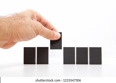 Man hand pick one of wood block from many wood block in row, metaphor to business concept in choose ideal person from many candidate. White background, side view.