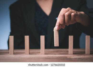 Man hand pick one wood block from many wood block to business concept in choose idea person from many candidate and different  Select resources Of the best and most outstanding companies