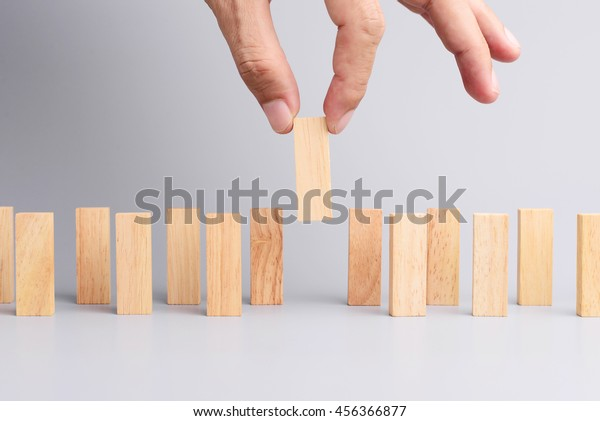 Man hand pick one of wood block from many wood block in row, metaphor to business concept in choose ideal person from many candidate. Gray background, side view.