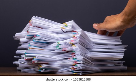 Man hand pick up Stack overload document report paper with colorful paperclip place on black background, business and paperless concept.
