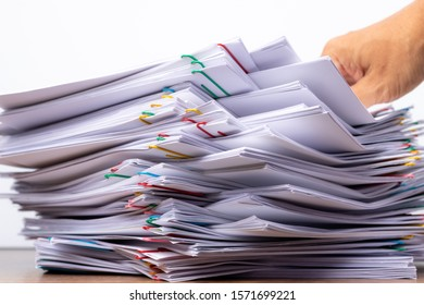 Man hand pick up Stack overload document report paper with colorful paperclip place on white background, business and paperless concept.