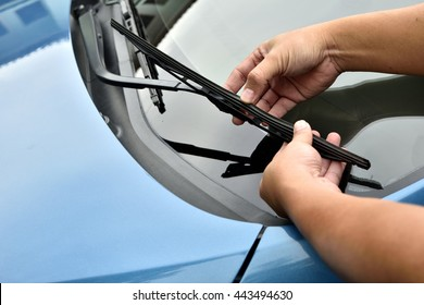 man hand picking up windscreen wiper or Mechanic check old wiper blade on customers sedan car.