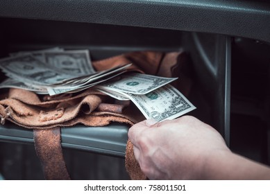 man hand pickup money from storage compartment  in car