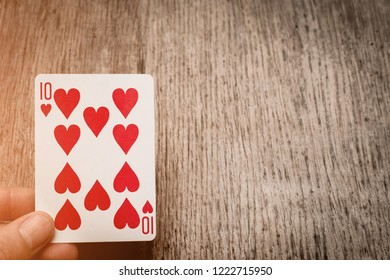 man hand and playing card ten of hearts copyspace