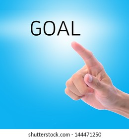 Man hand pointing on word, goal, with blue background.
