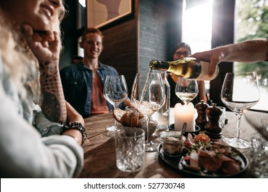 Man hand pouring white wine from the bottle into glasses with friends sitting around the table. Group of young people having food and drinks at restaurant.