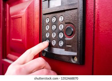 Man hand presses a button doorbell or intercom