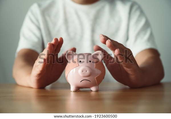 Man hand protect piggy bank on wood table. Save money and financial investment