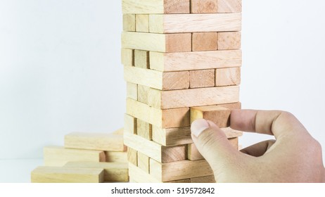 man hand pulling out the wooden block close up