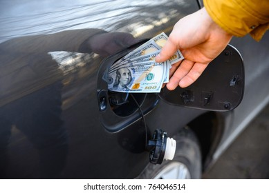 man hand put money to opening fuel tank of the car