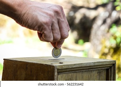 A man hand putting coin into a wooden box as donation