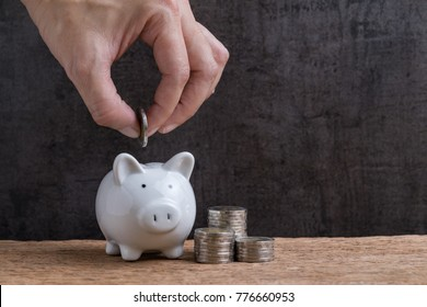 Man hand putting coin into piggy bank with stack of coins towers beside on wooden table and dark black background with copy space using as business or financial saving concept.