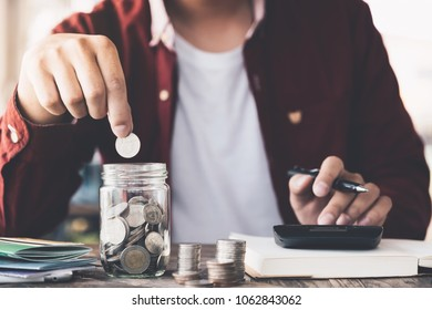 Man hand putting money (coin) in the glass jar during use calculator for calculate income or tax - Financial Business Concept