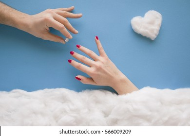 Man hand putting ring on women's finger, in a heavenly scenery with a heart and clouds made from cotton wool, on a blue sky paper background.