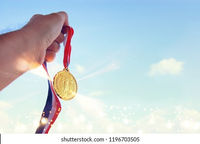 man hand raised, holding gold medal against sky. award and victory concept