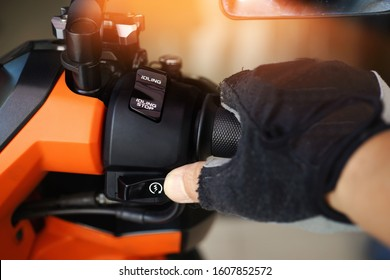 Man hand rider in a Motorcycle Gloves holding handlebar and pressing the Start,Stop Engine Buttons on motorcycle in garage,Things To Do Before Starting motorcycle concept