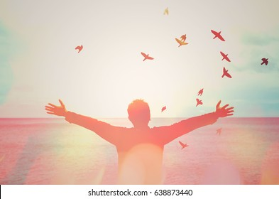 man hand rising and birds flying double exposure with colorful bokeh light on beach abstract texture background feel good and freedom travel adventure concept vintage tone color style