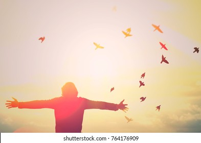 man hand rising and birds flying on sky abstract background. feel good and freedom concept. vintage tone color style
