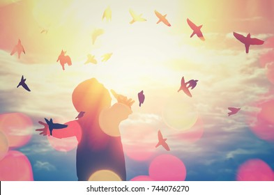 man hand rising on blue sky double exposure with colorful bokeh light and birds flying abstract background. Freedom and feel good concept. Vintage tone color style style