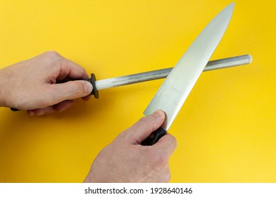 man hand sharpenes knife on yellow background. Knife sharpening using a knife grinder. Honing steel.