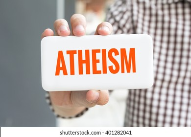 Man hand showing ATHEISM word phone with  blur business man wearing plaid shirt.