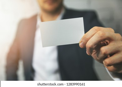 man hand showing blank white business card in front