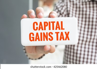 Man hand showing CAPITAL GAINS TAX word phone with  blur business man wearing plaid shirt.
