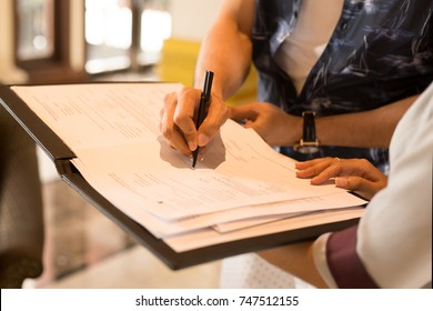 Man hand signing agreement from for hotel reservation