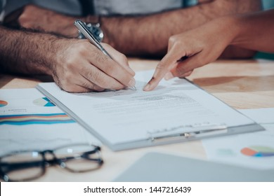 Man hand signing a contract on document for building house economic with architect and partner. select focus. Contract Concept