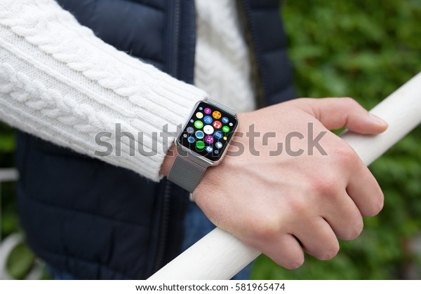 Man hand and smart touch watch with home screen icons apps on street