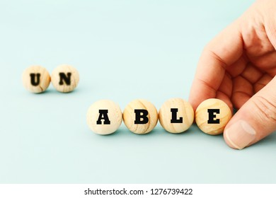 man hand spelling the text unable with wooden beads, taking out the word un so it written able. success and challenge concept